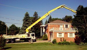 Photo of an APEX Concrete Pump reaching over a 2-story house